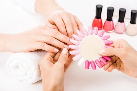 Partial view of manicurist holding pink nail polish palette Stock Photo