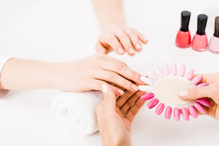 Cropped view of manicurist holding nail polish palette while choosing color