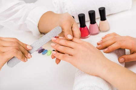 Cropped view of woman holding hand on towel while manicurist doing nail form