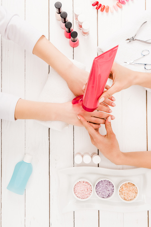 Top view of manicurist using hand cream on wooden surface