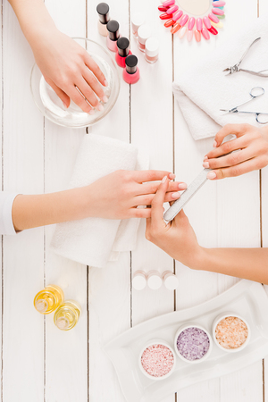 Top view of woman dipping hand in water while manicurist using nail file