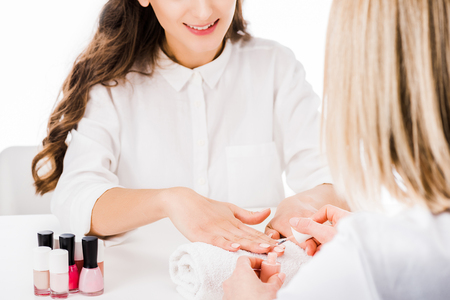 Cropped view of brunette woman smiling while manicurist applying nail polish isolated on white