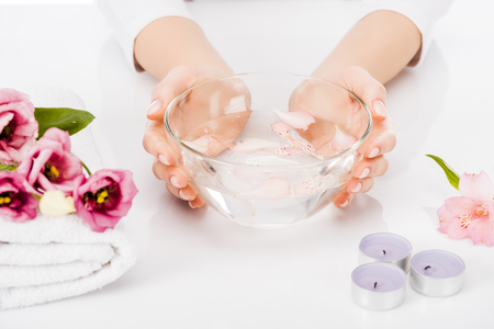 Partial view of manicurist using bowl with water for nail bath