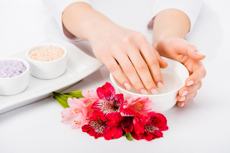 Partial view of woman taking nail bath with flowers Zdjęcie Seryjne