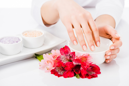 Partial view of woman with perfect manicure doing hand treatment
