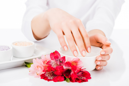 Cropped view of manicurist with colorful flowers isolated on white