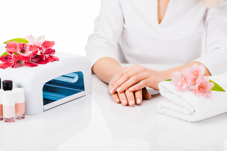 Partial shot of manicurist with towel and nail polish isolated on white