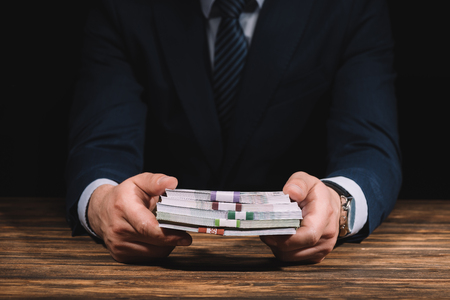 mid section of businessman holding russian rubles banknotes above wooden table