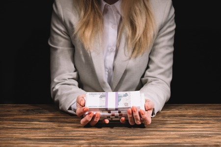 mid section of businesswoman holding russian rubles banknotes at wooden table on black