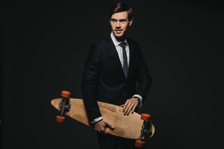 handsome businessman holding skateboard in hands isolated on black