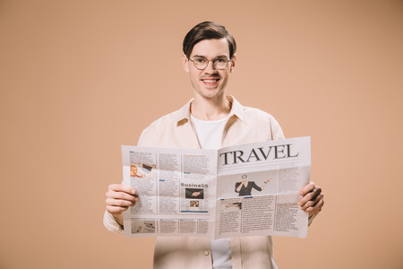 cheerful man reading travel newspaper isolated on beige 스톡 콘텐츠