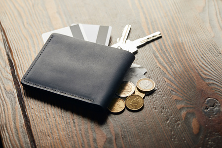 leather wallet, keys, cheque, coins and credit cards on wooden table Stockfoto