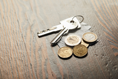 keys, cheque and coins on wooden table with copy space