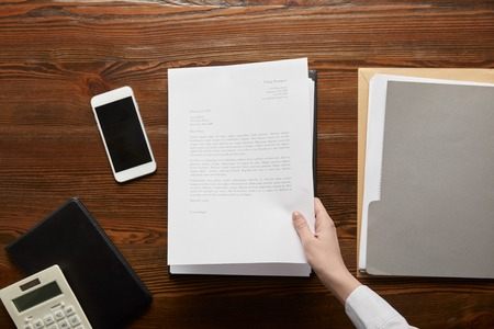 partial view of businessman holding document at workplace with copy space