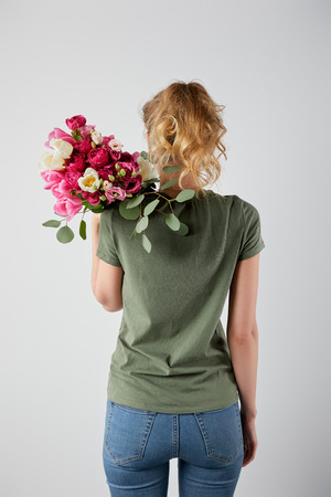 back view of girl holding bouquet with tulips and roses isolated on grey