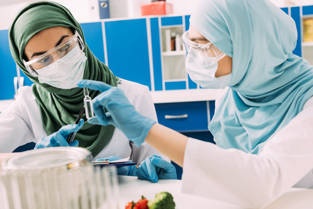 female muslim scientists in medical masks holding glass ampoule during experiment in chemical laboratory Reklamní fotografie