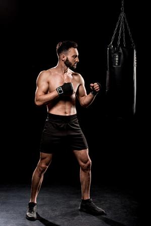 handsome boxer kicking boxer bag on black background Standard-Bild