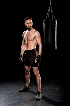 muscular boxer looking at punching bag on black background Stock Photo