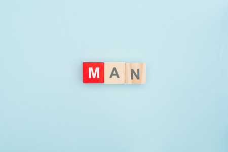top view of man lettering made of wooden blocks on blue background