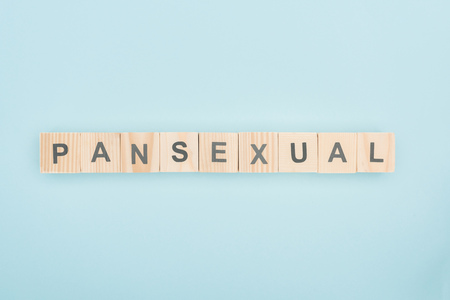 top view of pansexual lettering made of wooden cubes on blue background