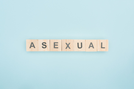 top view of asexual lettering made of wooden cubes on blue background Reklamní fotografie