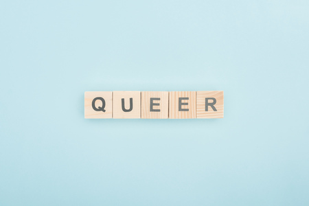 top view of queer lettering made of wooden cubes on blue background