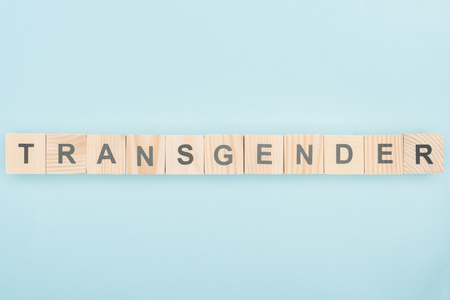 top view of transgender lettering made of wooden cubes on blue background