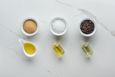 top view of bottles and bowls with various components for handmade cosmetics on white surface