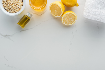 top view of lemons, honey, oat flakes and various ingredients for cosmetics making on white surface