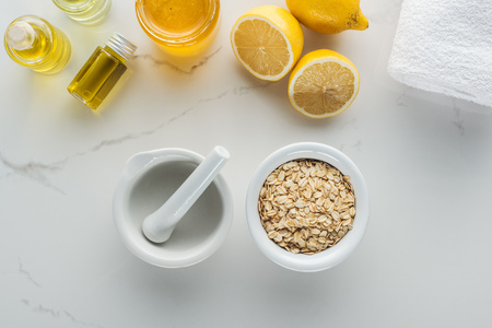 top view of bowl with oat flakes, pounder, lemons and various components for homemade cosmetics on white surface