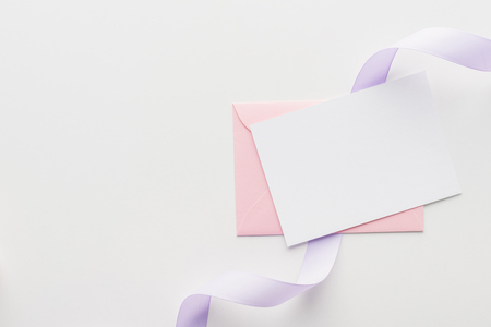 top view of empty blank with pink envelope and purple silk ribbon on grey background