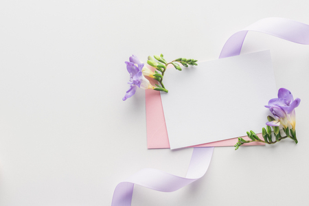 top view of empty blank with pink envelope, purple flowers and silk ribbon on grey background