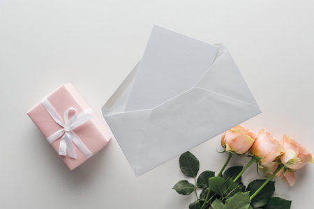 top view of pink roses, wrapped gifts, envelope and card on grey background Stock Photo
