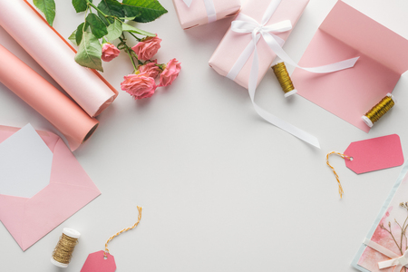top view of pink roses, rolls of paper, wrapped gifts, envelope and greeting card on grey background