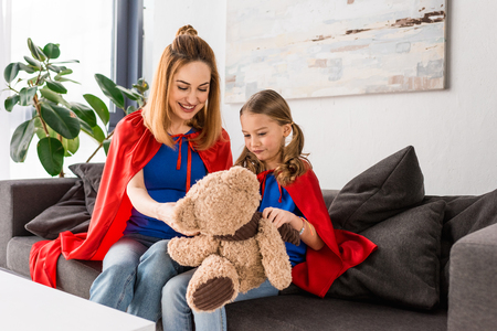 smiling mother and kid in red cloaks holding teddy bear Фото со стока - 117910051