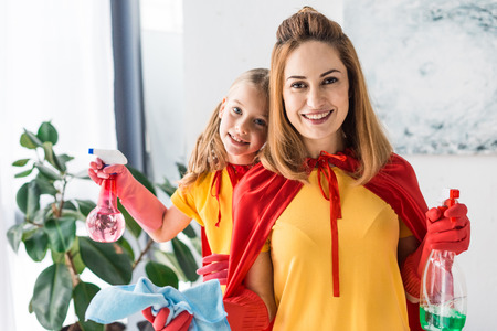 Mother and daughter in red capes and rubber gloves with sprays cleaning and looking at camera