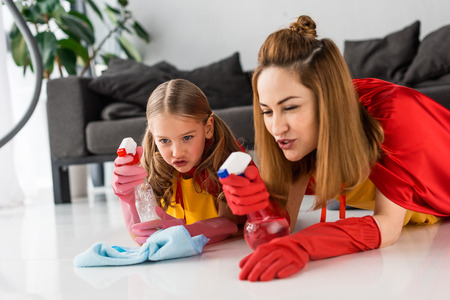 Mutter und Tochter in roten Umhängen und Gummihandschuhen waschen den Boden zu Hause floor Standard-Bild