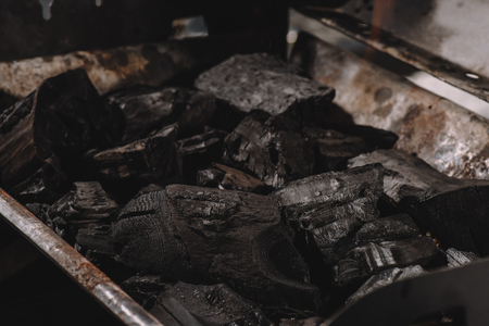pile of dark black coals in iron barbecue Фото со стока