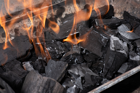 bright burning black coals in iron barbecue grill
