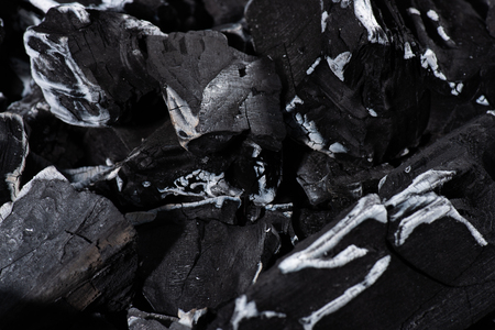 close up of black burnt textured charcoal with white ash