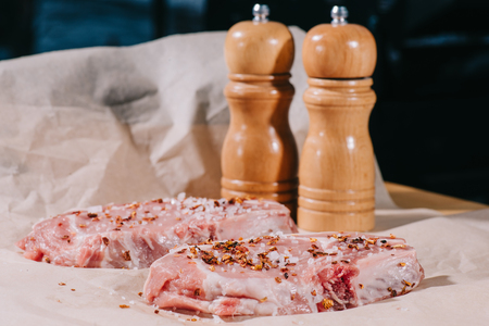 selective focus of raw fresh steaks with seasoning and salt and pepper mills on paper