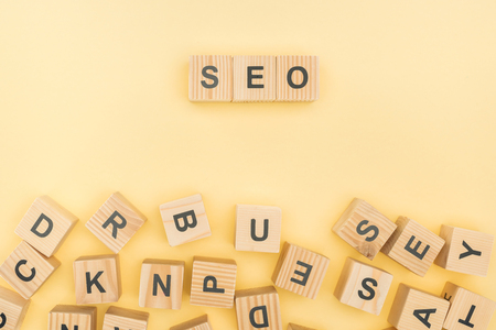 top view of seo lettering with wooden cubes on yellow background