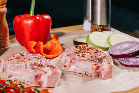 close up of raw juicy steaks with seasoning and fresh ripe vegetables on paper Stockfoto