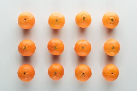flat lay with bright ripe orange tangerines on white background