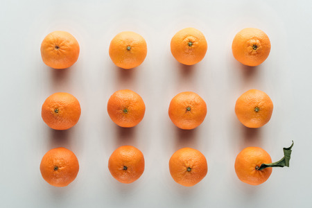 flat lay with bright ripe orange tangerines and one with green leaves