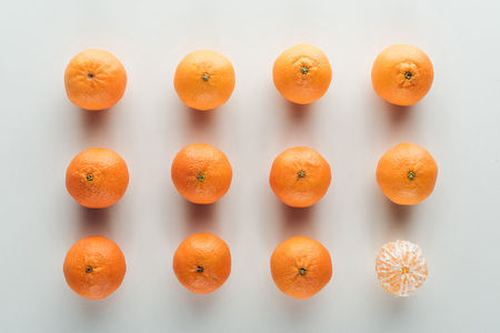 flat lay with bright ripe orange tangerines with peeled one
