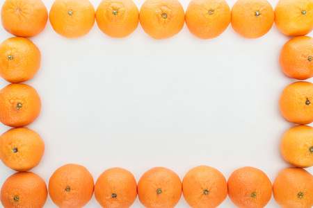frame borders of ripe tangerines on white background with copy space