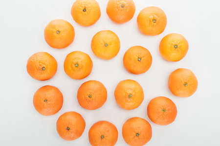 top view of ripe orange tangerines arranged in circle on white background