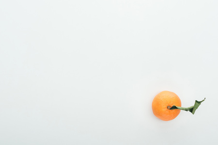 bright ripe orange tangerine with green leaves on white background with copy space