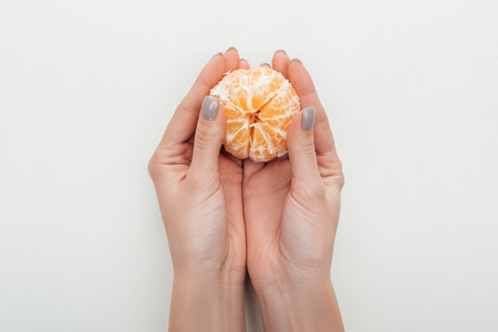 partial view of woman holding peeled whole tangerine on white background